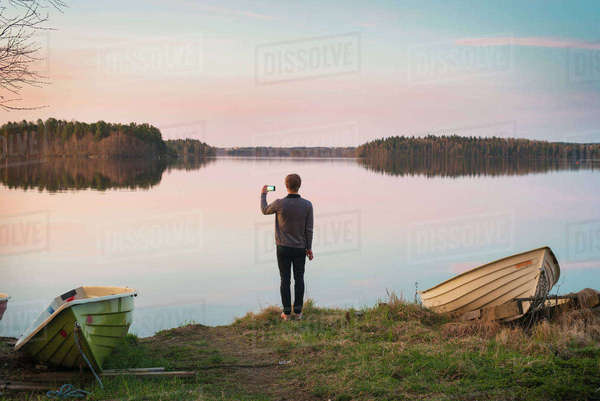 Finland, Pirkanmaa, Tampere, Pyhajarvi, Mid adult man taking pictures on lake shore Royalty-free stock photo