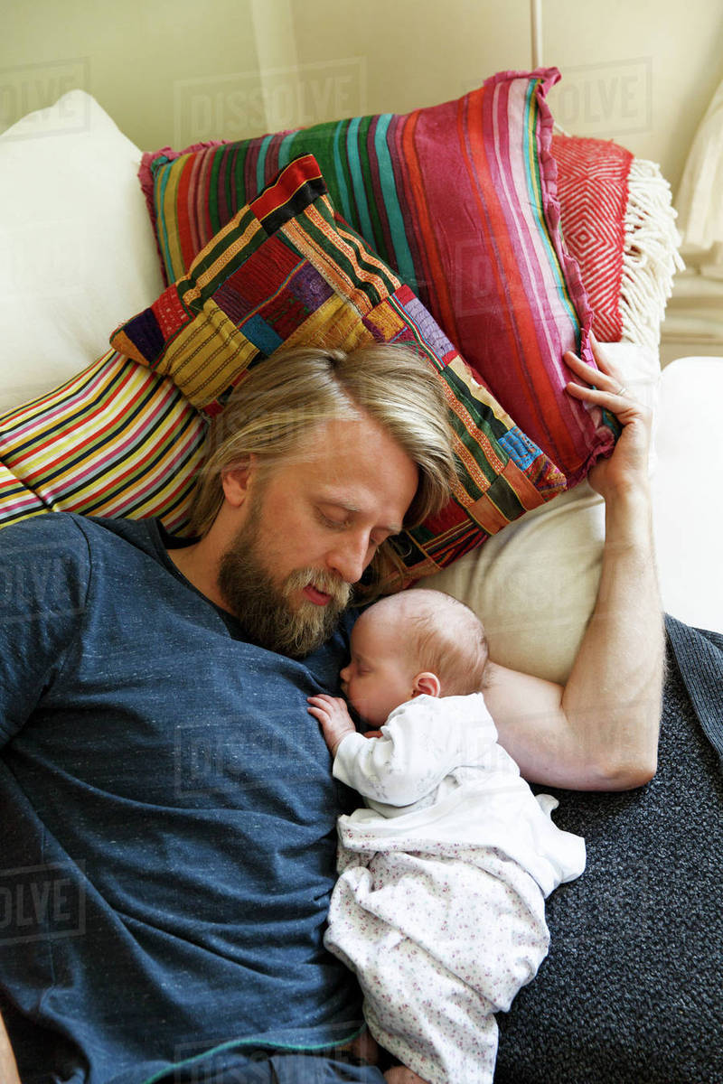 Sweden father sleeping with newborn daughter 0 1 months on sofa