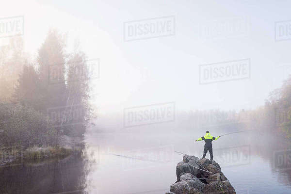 Sweden, Vastmanland, Bergslagen, Torrvarpen, Young man fishing in lake on foggy day Royalty-free stock photo