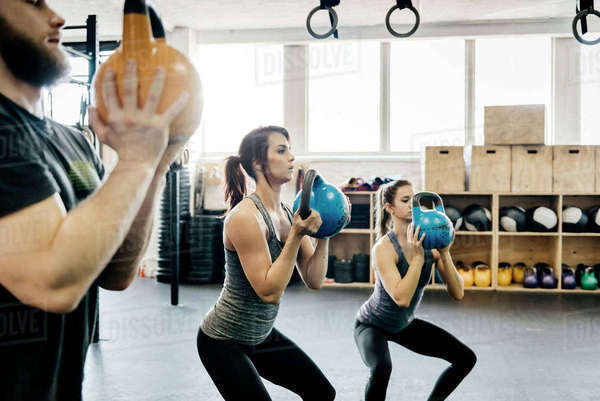Germany, Young women and man cross training with kettlebells in gym Royalty-free stock photo