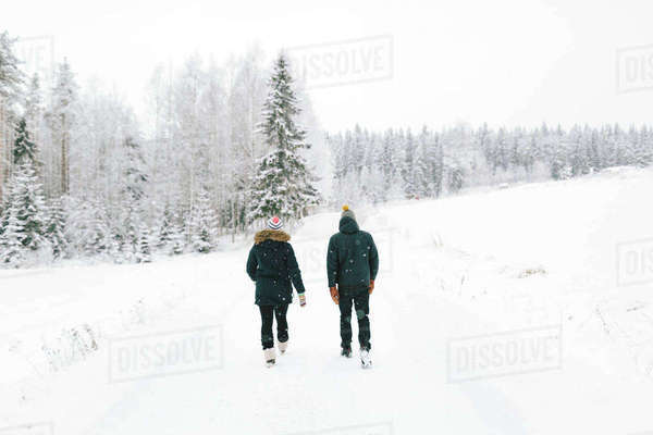 Finland, Jyvaskyla, Saakoski, Young couple walking along road covered with snow Royalty-free stock photo