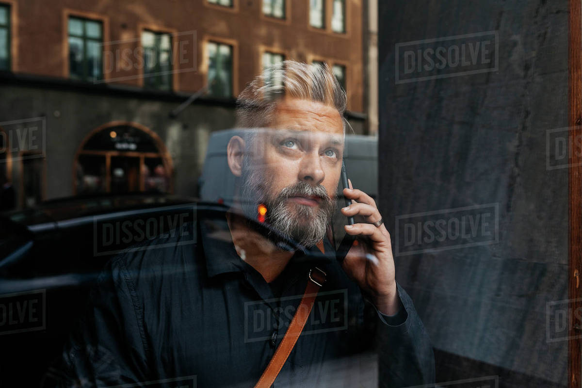 Man on smart phone through window in Sweden Royalty-free stock photo