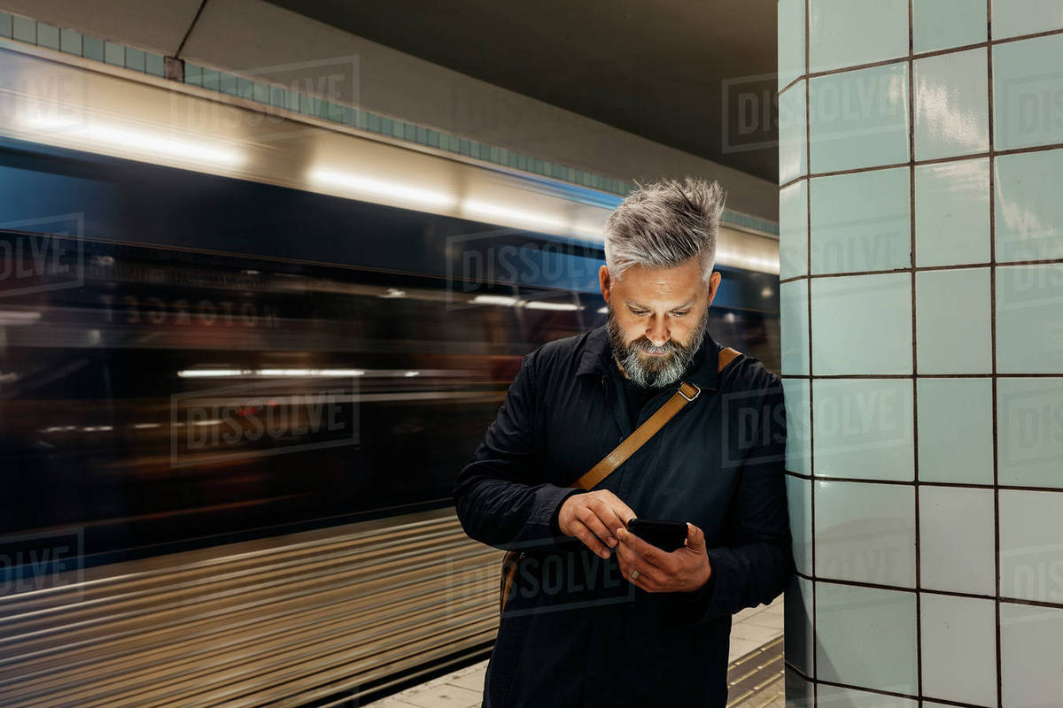 Man texting at train station in Stockholm, Sweden Royalty-free stock photo