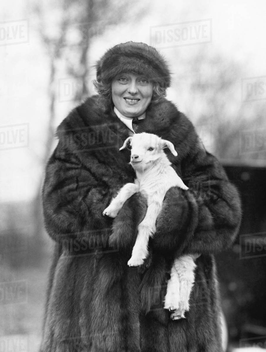 2690303ed Woman in a fur coat and hat holding a small baby lamb in her arms ...