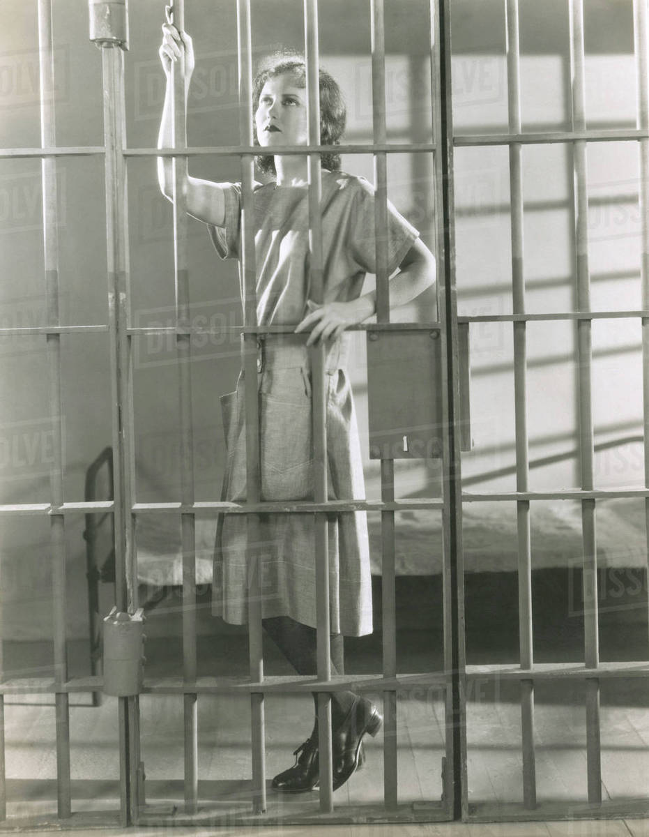 young woman standing in prison cell stock photo dissolve