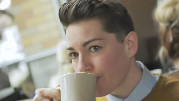 Slow motion shot of a genderqueer person drinking from a mug in a cafe Royalty-free stock video