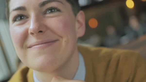 Hand-held shot of a smiling genderqueer person sitting in a cafe Royalty-free stock video