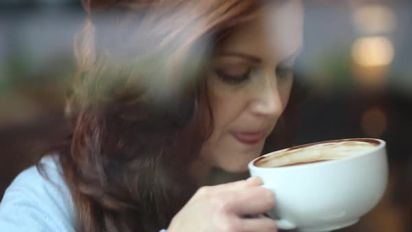 Hand-held shot of a woman drinking a hot drink at an indoor cafe Royalty-free stock video