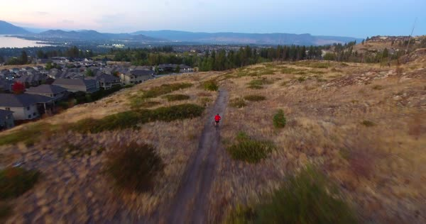 Aerial view of mountain biker on trail with city and lake in background Royalty-free stock video