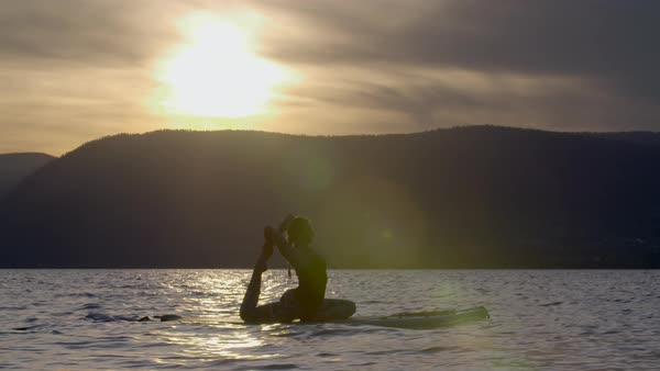 Silhouetted view of a woman doing yoga on a paddleboard in Okanagan Lake Royalty-free stock video