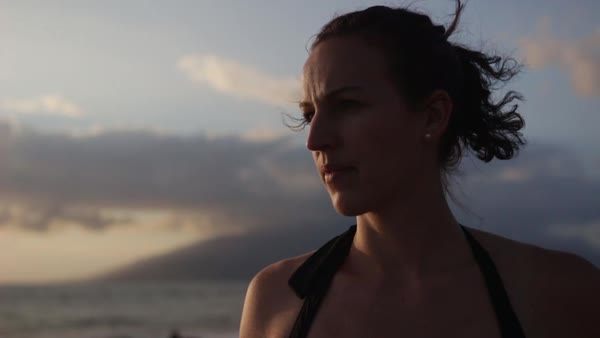 Hand-held shot of a woman standing on a beach and looking away Royalty-free stock video