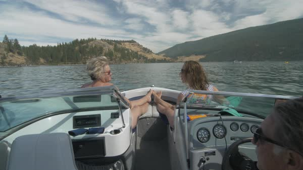 Locked-off shot of two women enjoying view of lakeshore on a motorboat Royalty-free stock video