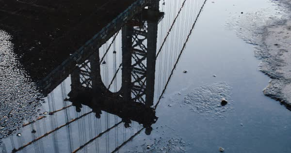 An establishing shot of New York City's Manhattan Bridge reflected in a puddle after a Thunderstorm Royalty-free stock video