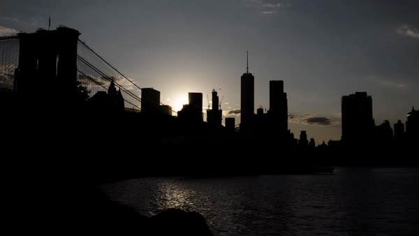 An establishing shot of New York City's Freedom Tower and Brooklyn Bridge at sunset Royalty-free stock video