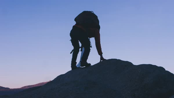 A hiker climbs a precipice carrying a flag Royalty-free stock video