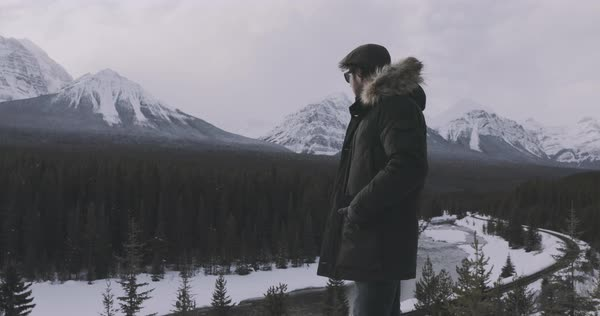 Slow motion shot of a man looking at the snowy mountains on a beautiful winter day Royalty-free stock video