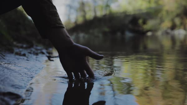 Slow motion of hand of a man touching water surface Royalty-free stock video