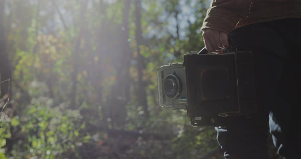 Hand-held shot of a man holding a vintage camera in a forest Royalty-free stock video
