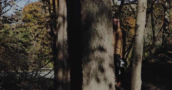 Hand-held shot of a man standing in a forest with a camera Royalty-free stock video