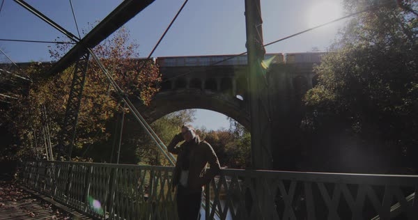 Gimbal shot of a man standing by railing of a bridge Royalty-free stock video