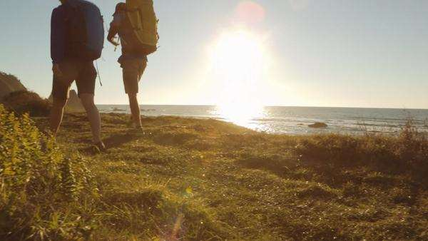 Wide shot of couple hiking along a coast Royalty-free stock video