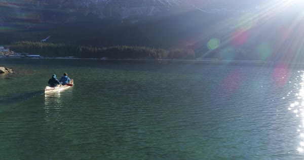 Two men paddling a canoe at a mountain lake Royalty-free stock video