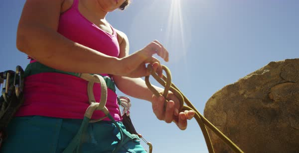 Hand-held shot of a woman tying a rope to her harness before rock climbing Royalty-free stock video