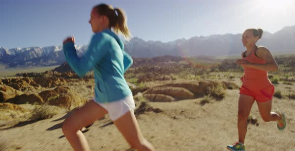 Tracking shot of two women running in a rocky desert Royalty-free stock video