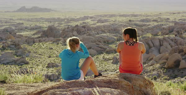 Static shot of two women sitting on rocks and enjoying view of rock formations Royalty-free stock video