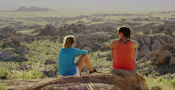 Static shot of two women talking and enjoying view of rock formations Royalty-free stock video