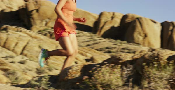 Tracking shot of two women running on rocky terrain Royalty-free stock video