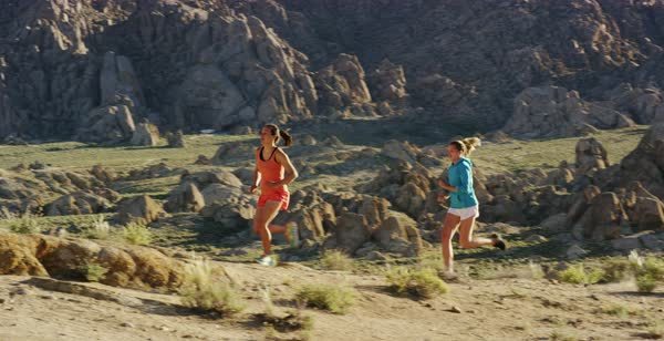 Slow motion shot of two women running on rocky terrain in Alabama Hills Royalty-free stock video