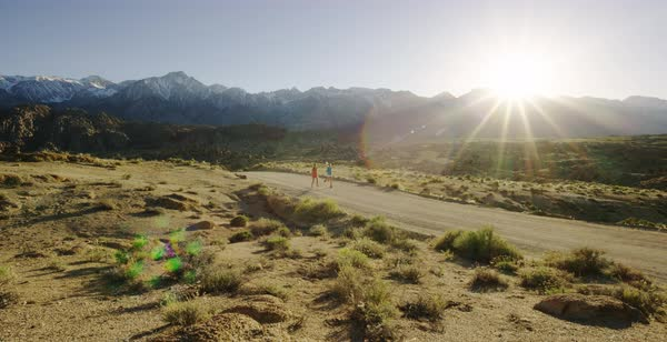 Tracking shot of two women running on a dirt road in Alabama Hills Royalty-free stock video