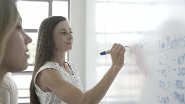 Hand-held shot view of a Caucasian woman writing ideas on a whiteboard at the office Royalty-free stock video
