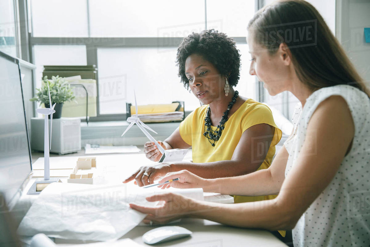 Two female office workers working together on a wind energy project Royalty-free stock photo