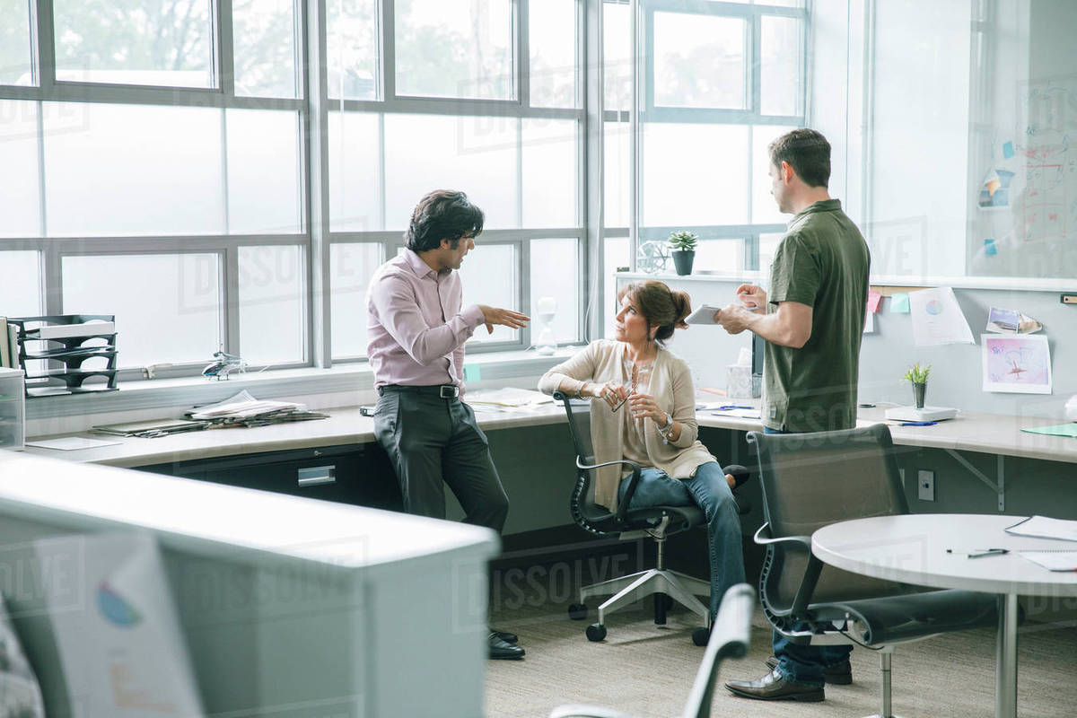 Three coworkers talking in an office Royalty-free stock photo