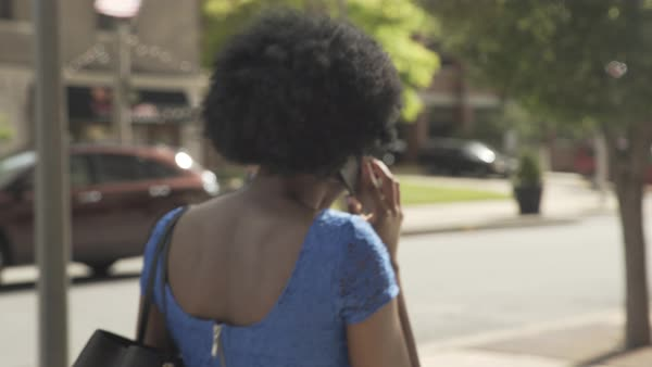 Tracking shot of a woman talking on her cell phone on a street Royalty-free stock video