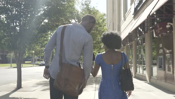 Tracking shot of a couple looking at a cell phone while walking on a sidewalk Royalty-free stock video