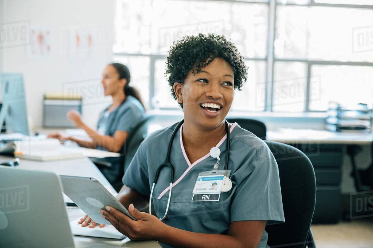 Smiling nurse holding digital tablet Royalty-free stock photo