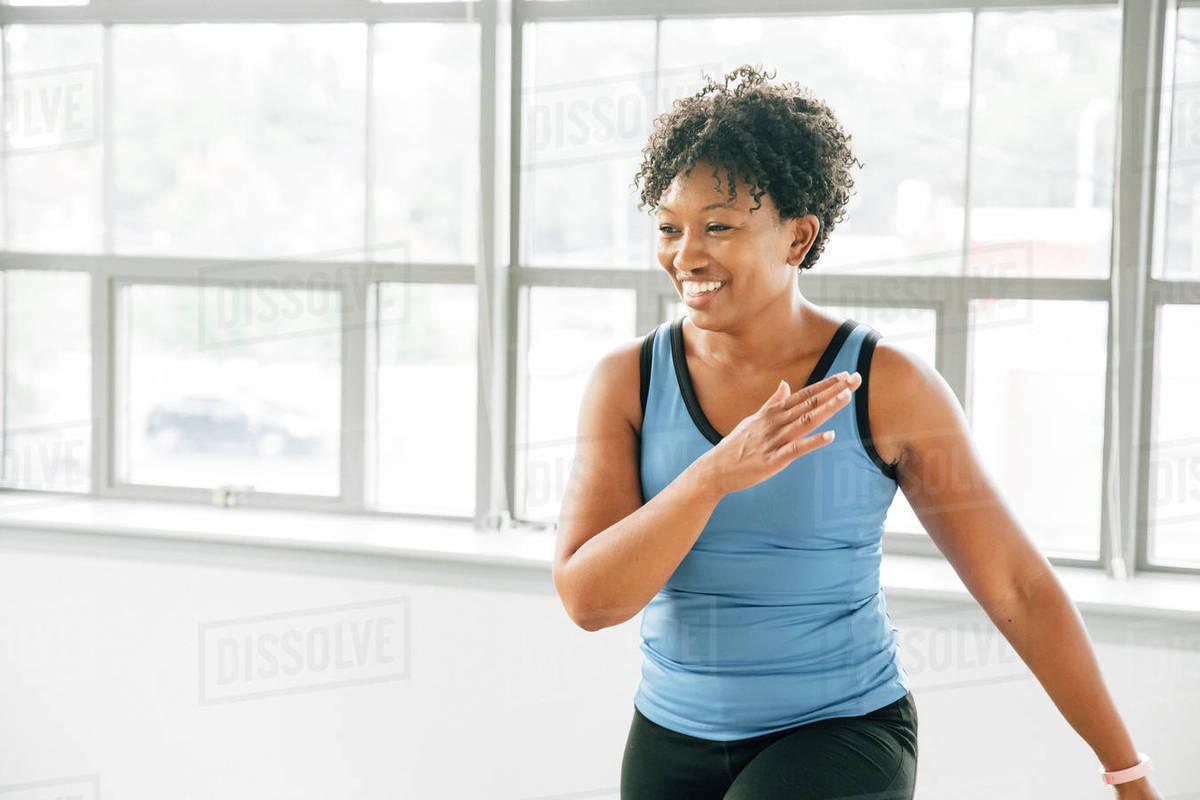 Woman exercising near window in studio Royalty-free stock photo