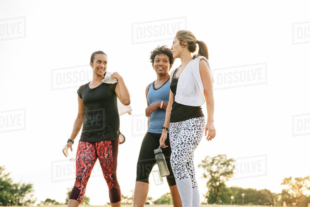 friends walking and talking outdoors after exercise stock photo