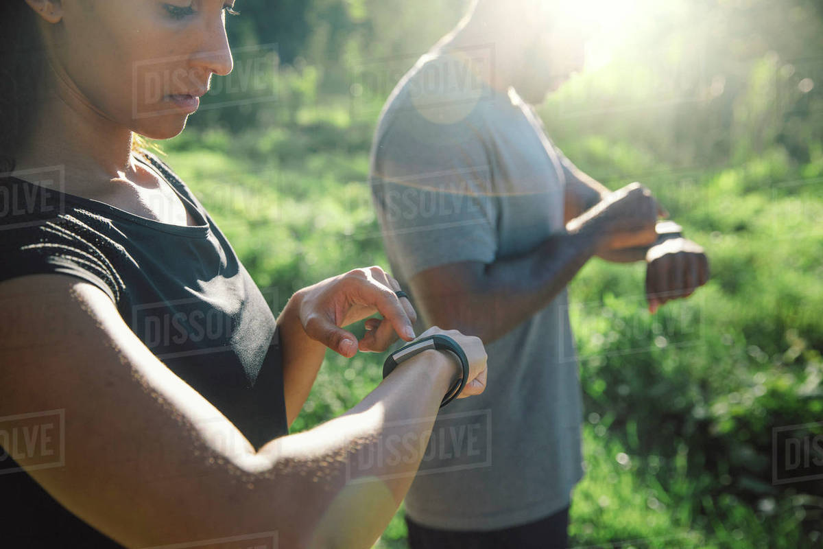 Couple setting smart watches on path in park Royalty-free stock photo