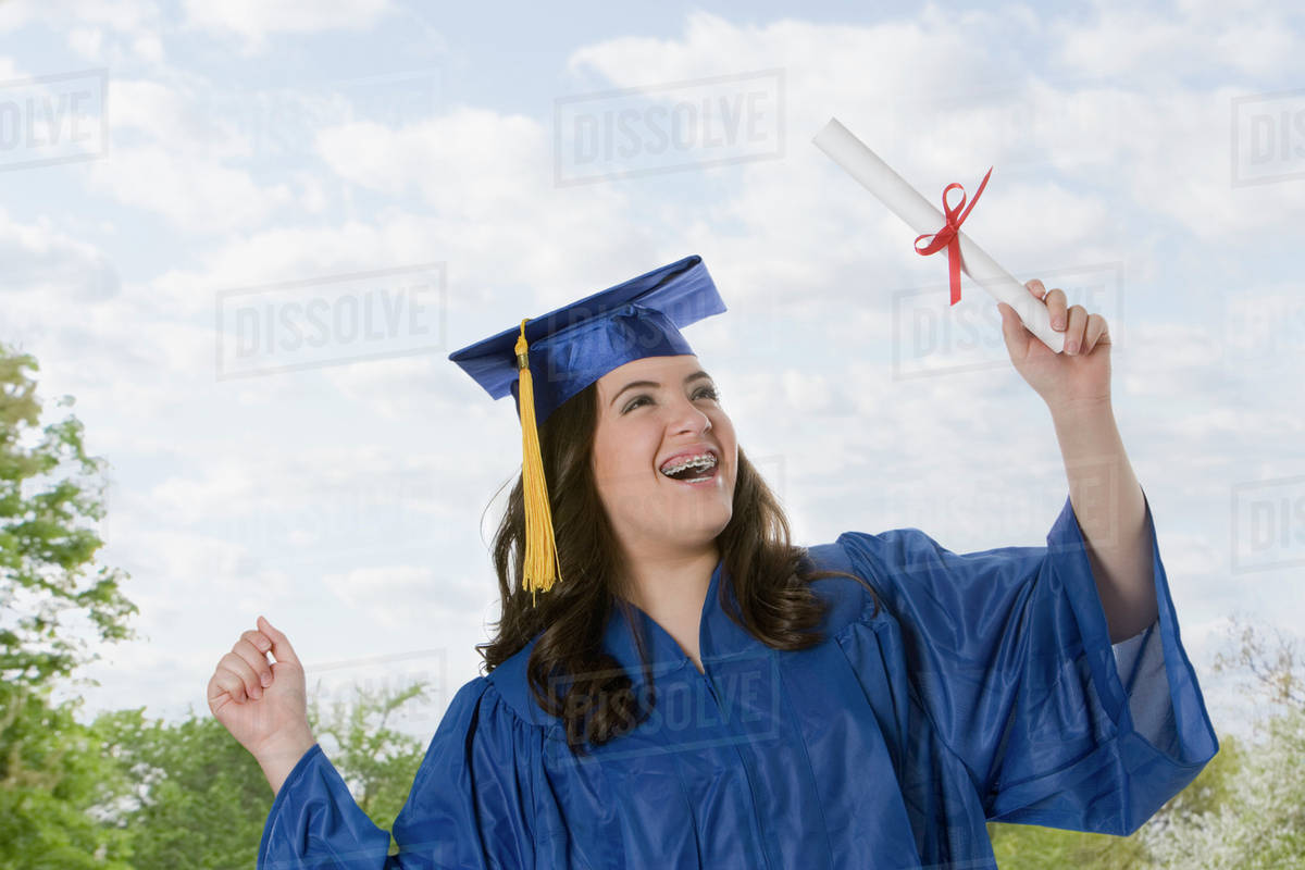 Hispanic teenage girl in graduation cap and gown holding diploma ...