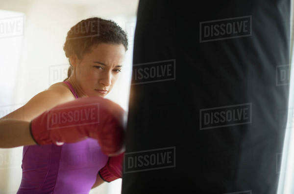Mixed race woman hitting punching bag in gym Royalty-free stock photo