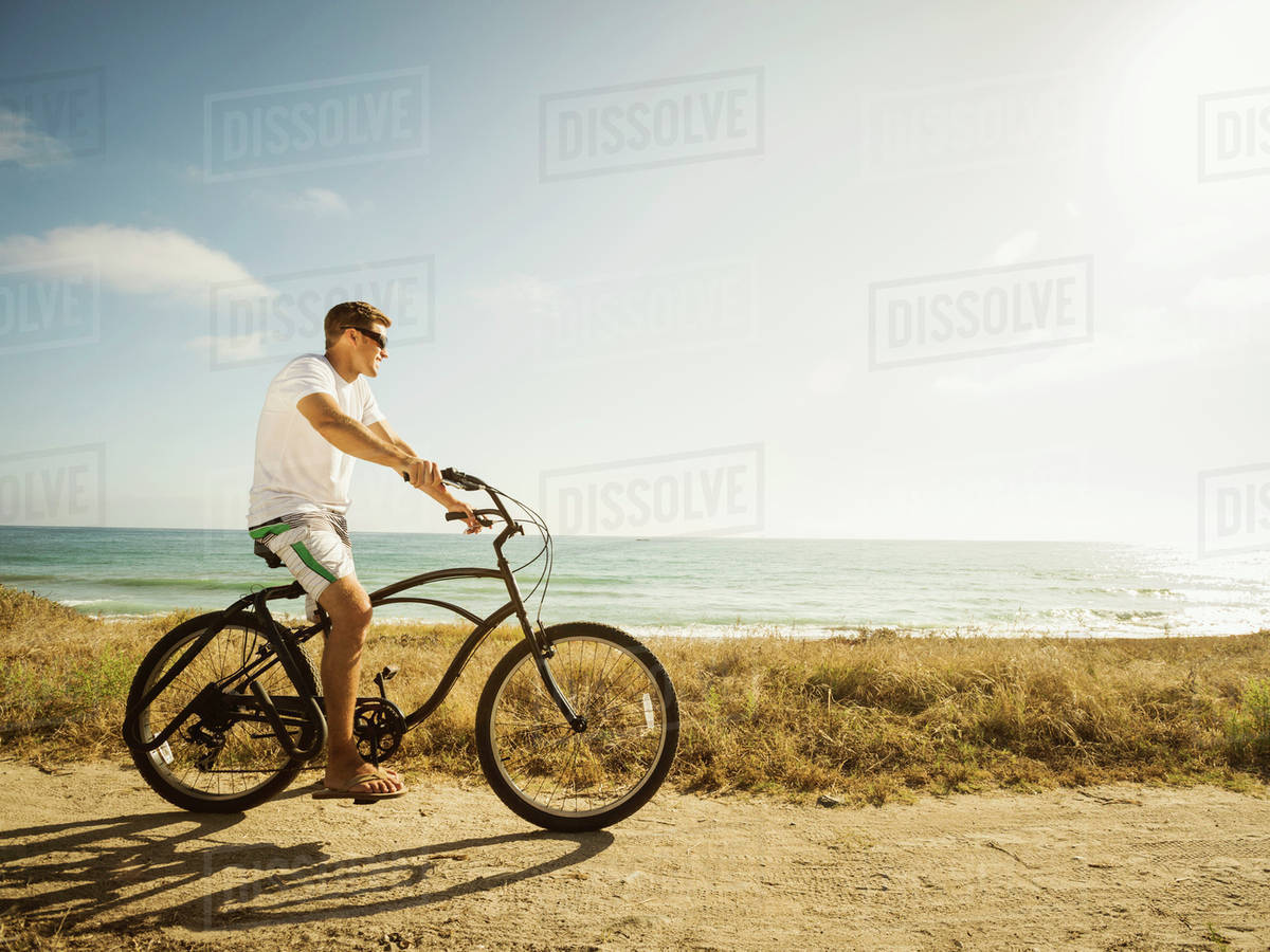 Caucasian Man Riding Bicycle On Beach