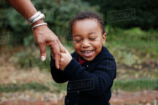 African American boy holding hand of mother in park Royalty-free stock photo