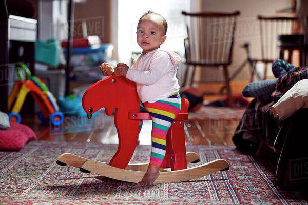 Mixed race baby girl playing on rocking horse Royalty-free stock photo