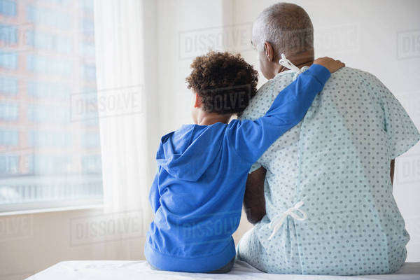 Mixed race grandfather sitting with grandson in hospital Royalty-free stock photo