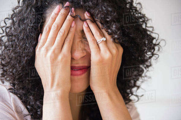 Mixed race woman with curly hair covering her face Royalty-free stock photo