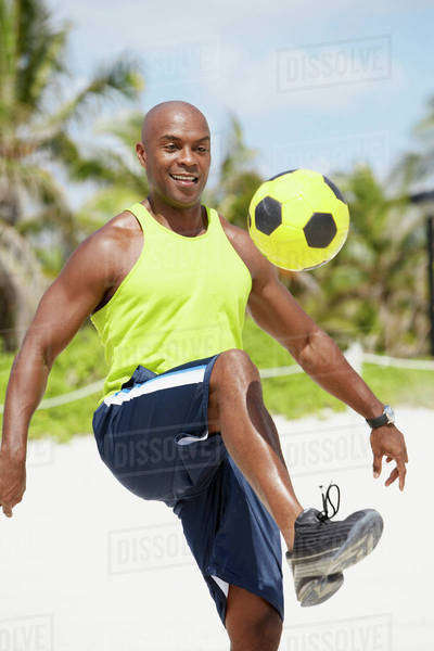 African American man bouncing soccer ball on knee Royalty-free stock photo